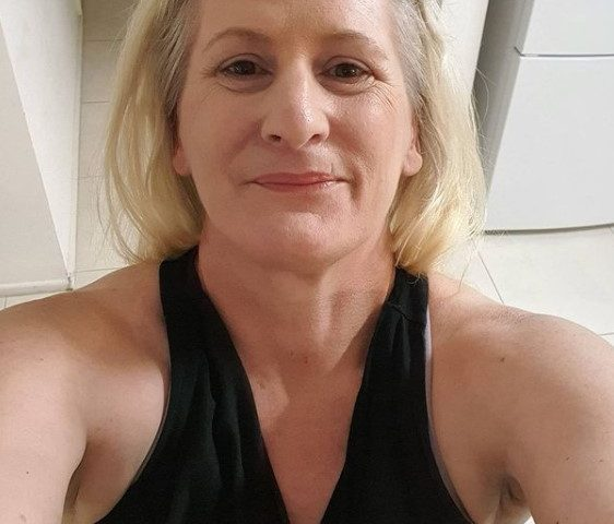 Plava matorka u crnoj majci sa golim ramenima