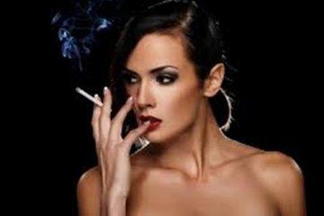 Crnka golih ramena puši cigaretu